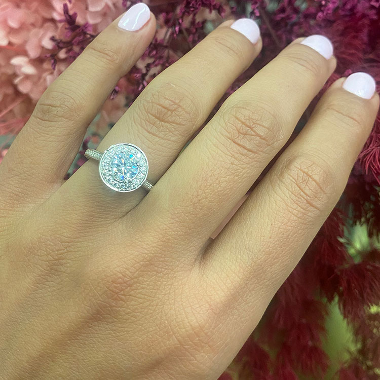 Round brilliant cut diamond set in a 3D halo engagement ring